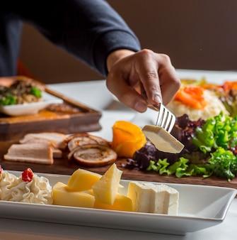 Человек берет сыр из сырной тарелки с белым сыром, чеддером, сливочным сыром