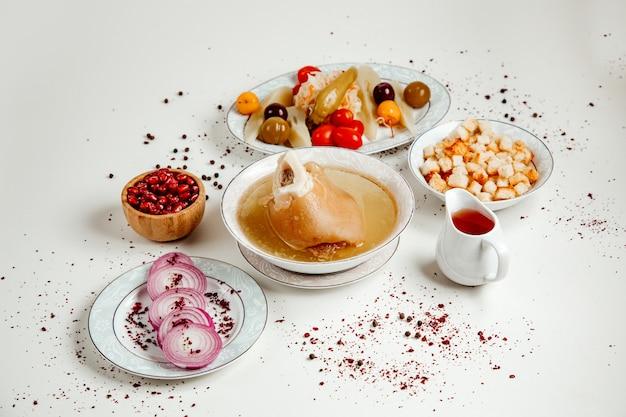 Суп из хаша с различными солеными огурцами и нарезанным луком