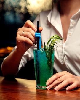 Женщина пьет синий коктейль с эстрагоном