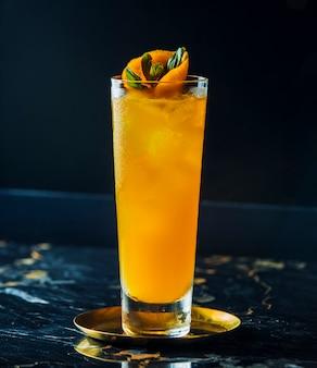 テーブルの上の氷とオレンジのカクテル