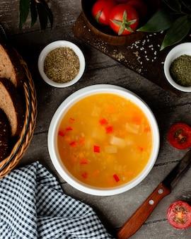 Куриный бульон с овощным супом в белой миске