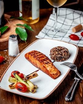 テーブルの上に野菜とフライドサーモン