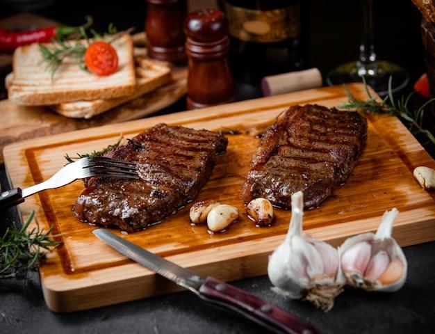 Жареные кусочки стейка на деревянной доске и чесноке