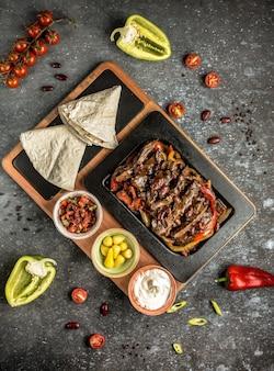 テーブルの上のラバッシュと肉ファヒータ