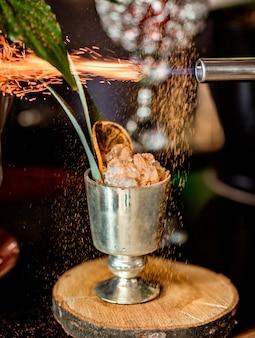 Зеркальный бокал коктейля со льдом, украшенный обожженной корицей