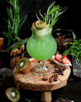 Уникальный стакан коктейля из киви, украшенный кусочками киви и эстрагоном