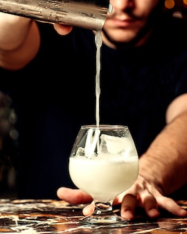 Бармен наливает коктейль в бокал