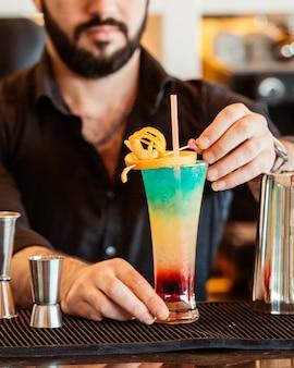 Бармен украшает красочный коктейль апельсиновой цедрой