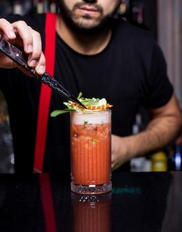 Бармен ставит апельсиновую цедру на стакан апельсинового и яблочного коктейля