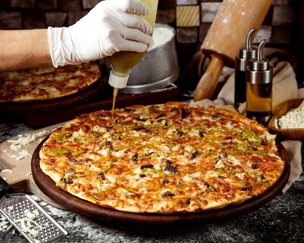 Шеф-повар добавляет соус песто к мясной пицце