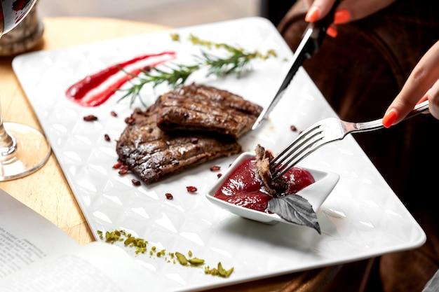 サワーソースにステーキの部分を浸す女性のクローズアップ