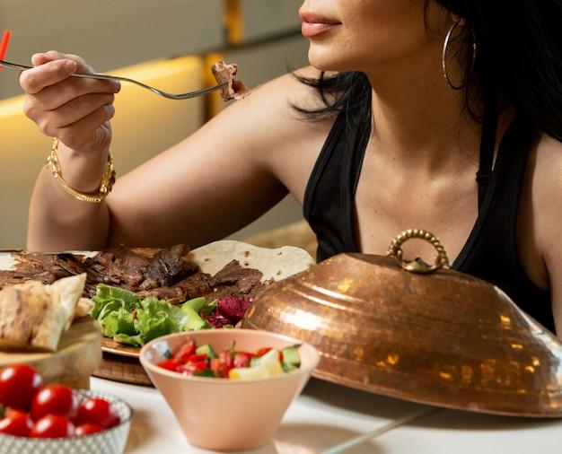 Крупным планом женщина ест ломтики донер ягненка, подается с салатом и лепешкой