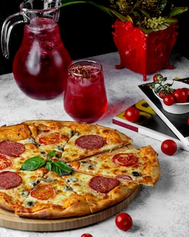 Нарезанная пицца пепперони с кусочками помидоров, сыром и соусом песто