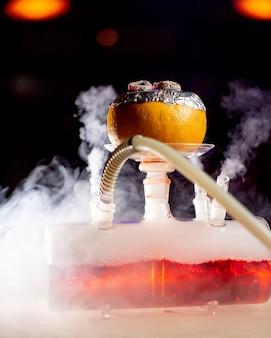 Дым выходит из грейпфрутового кальяна на стеклянной основе