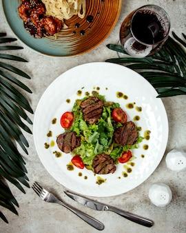 Вид сверху кусков жареной говядины с овощами и соусом песто