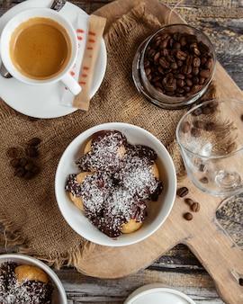 Вид сверху миски из профитроли с шоколадным соусом и кокосовой крошкой