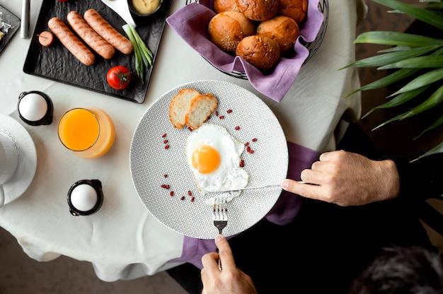 Вид сверху человека с завтраком с солнечной стороной вверх яйцо