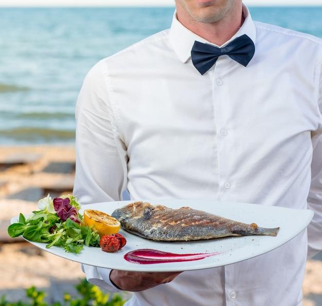Официант держит тарелку жареной рыбы с жареным лимоном, помидорами, свежим шпинатом, салатом