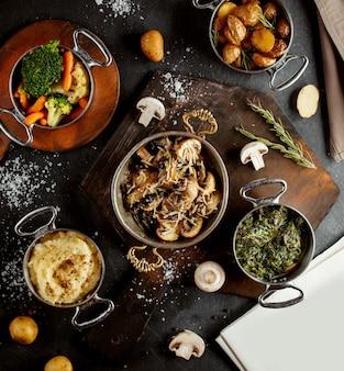 Вид сверху на сковородки с грибным пюре, сабзи, вареными овощами и жареным картофелем