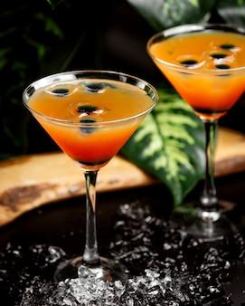 Два бокала цитрусового коктейля в бокалах для мартини с оливковым кубиком льда