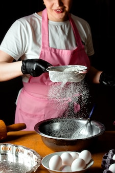 ケーキを作るためのボウルに女性ふるい花