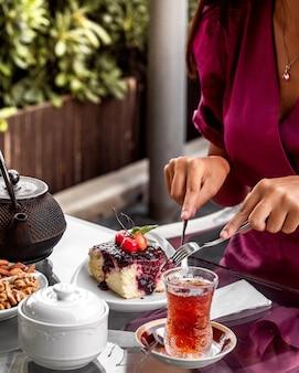 Женщина режет пирог с вишневым вареньем, подается со стаканом чая