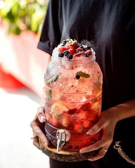 タップでガラスの瓶に果物の水を保持している女性