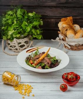 Салат из говядины с рукколой, помидорами, листьями салата и хлебной палочкой