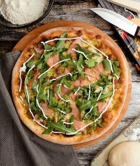 サーモンとテーブルの上のルッコラのピザ