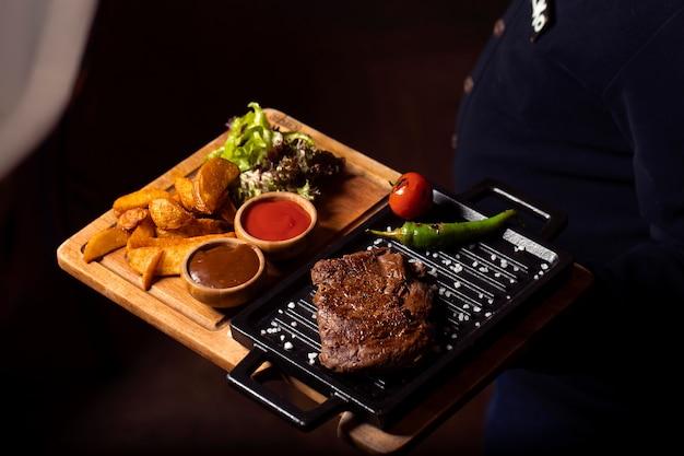 Стейк из говядины на мини-сковороде с жареным картофелем, свежим салатом