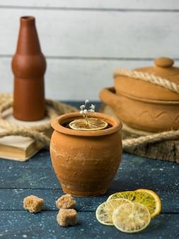 Глиняный горшок рядом с сушеными ломтиками лимона и кубиками коричневого сахара