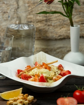 Салат из жареных креветок с листьями салата, ломтиком помидора и хлебной палочкой