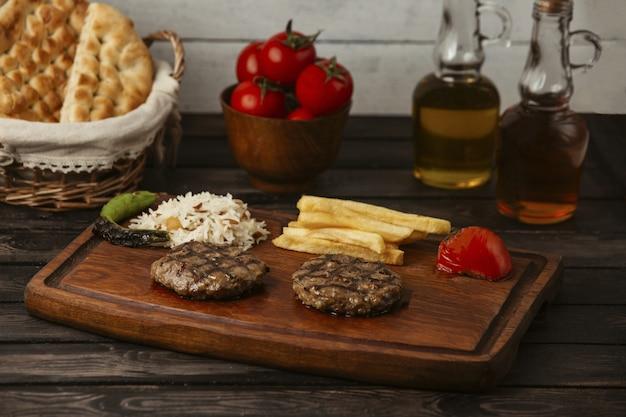 Котлеты из говядины на гриле, подается с рисом, картофелем фри, томатами на гриле и перцем