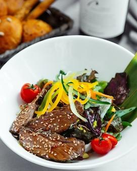 牛肉のスライスをテリヤキソースで調理し、ゴマを振りかけ、野菜を添えて