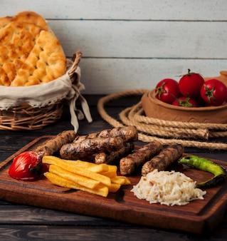 ビーフソーセージのグリル、ライス、フライドポテト、コショウ、トマト