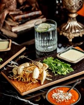 Кусочки куриного филе на палочке, подаются с рукколой и соусом