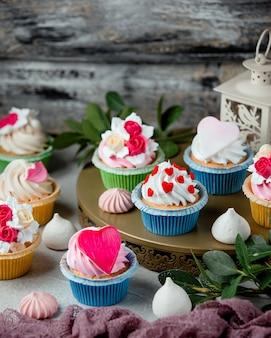 ホイップクリームの心と花で飾られたかわいいカップケーキ