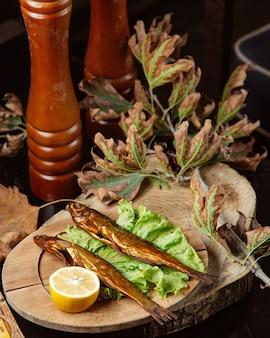 Рыба вяленого копчения подается с лимоном в деревянной тарелке