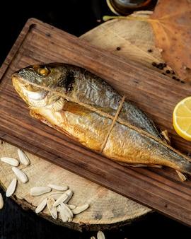 Рыба вяленого копчения, завернутая в веревку, подается с половиной лимона на деревянной доске
