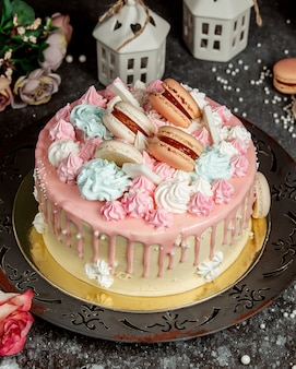 Пирожное с кремом розового цвета, украшенное розово-голубым кремом и миндальным печеньем