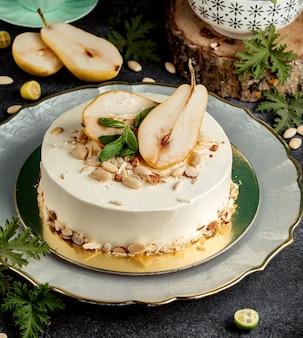 ナシの半分とアーモンドで飾られた丸いケーキ