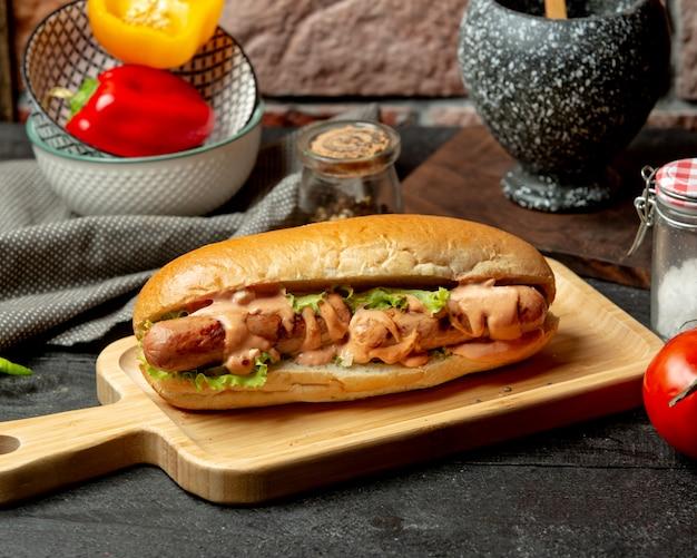 Бутерброд с колбасками с острым соусом и листьями салата