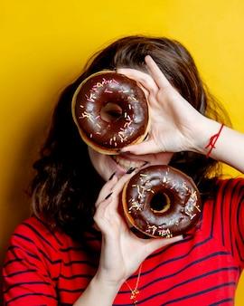 Женщина, держащая пару пончиков с шоколадом