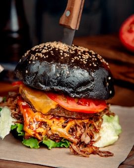 Черный гамбургер с ножом на столе