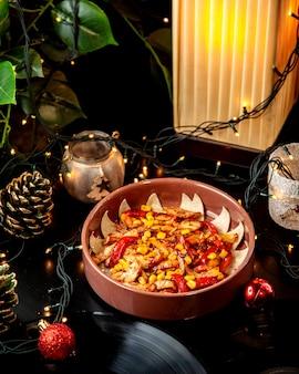 赤黄色ピーマンコーンとトマトソースのチキンファヒータ、陶器パンで提供