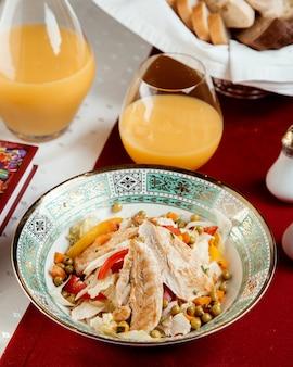 Куриный салат с перцем горошком и стаканом апельсинового сока