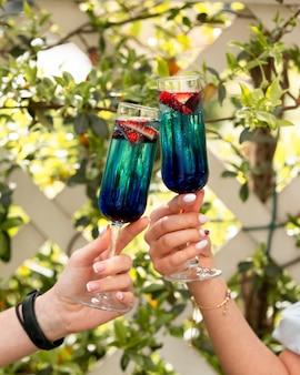 Два коктейля в бокале с кусочками фруктов