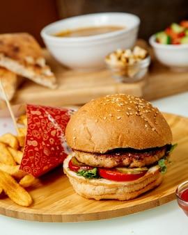 木の板にフライドポテトと肉のハンバーガー