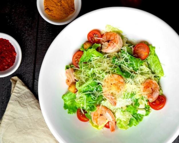 Салат из креветок цезарь с листьями салата, пармезаном, помидорами черри и начинкой из хлеба