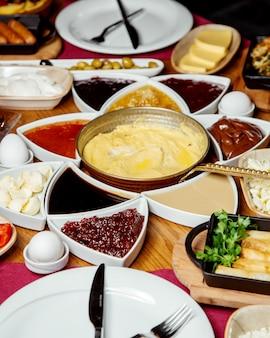 チーズジャム、卵料理、チョコレートバターなどのトルコ式朝食のセットアップ